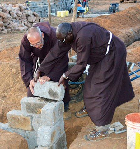 Father John and another Capuchin building a brick wall in Kithyoko